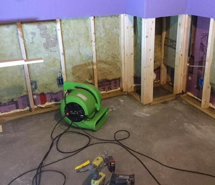 a basement with the lower portion of the walls cut out and green drying equipment near it