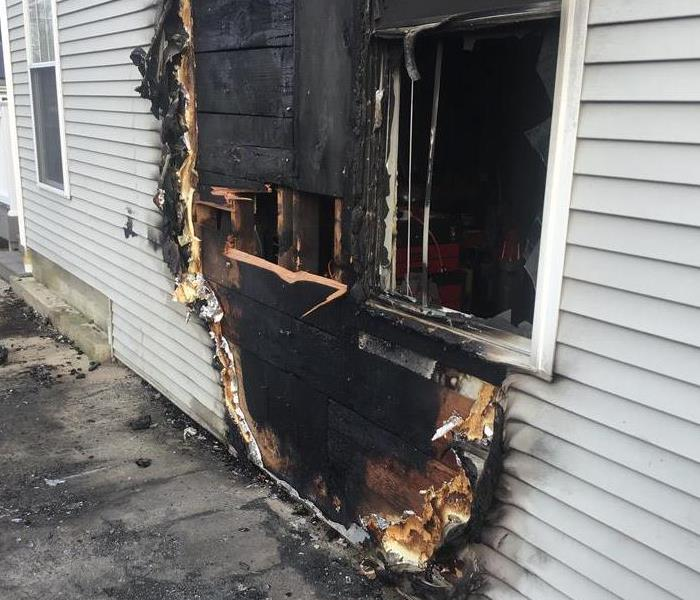 the exterior of a home with charred siding and an exposed hole