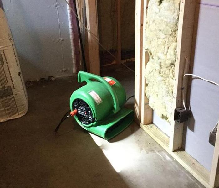 a green air mover in a basement with sheetrock cut from the bottom half of the wall