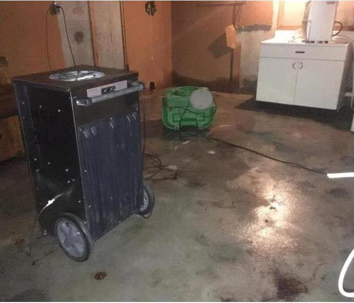 A dehumidifier and air mover drying up an affected area